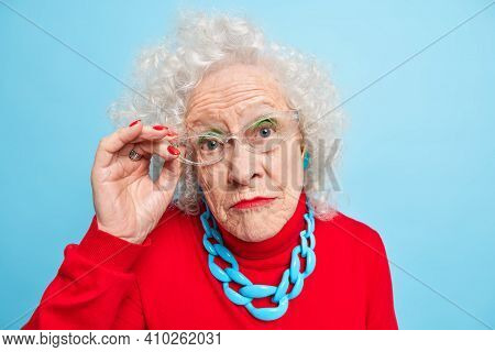 Portrait Of Beautiful Wrinkled Senior Woman Has Curly Grey Hair Bright Makeup Manicure Looks Attenti