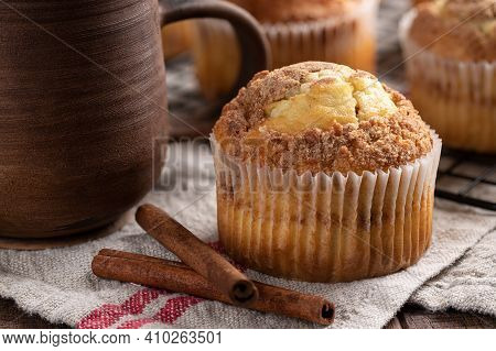 Closeup Of A Cinnamon Muffin Next To Coffee Mug With Muffins On A Wire Rack In Background