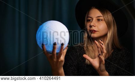 A Young Woman Fortune Teller In A Hat Is Holding A Magic Ball. Beautiful Psychic Woman Is Guessing W