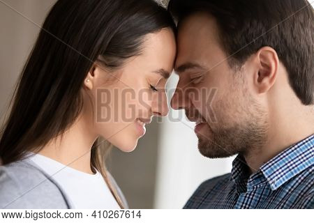 Happy Millennial Couple In Love Touching With Foreheads