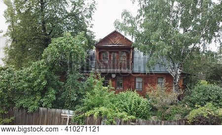 Old Wooden House In Greenery. Stock Footage. Old Residential Cottage Made Of Wood On Background Of G