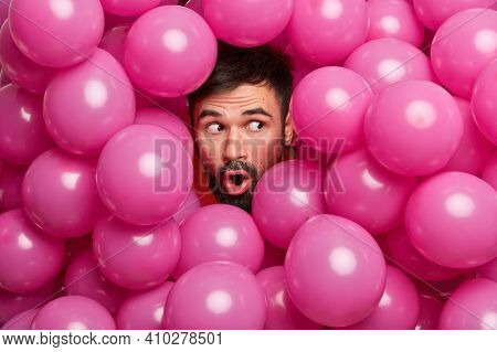 Surprised Bearded European Man Sticks Head Through Decorated Background With Inflated Balloons Prepa