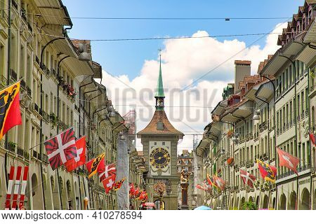 Bern, Switzerland - Aug 23, 2020: Kramgasse Street With Swiss Flags And Zytglogge Clock Tower And Za