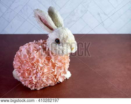 Easter Bunny Decor Sitting On A Terra-cotta Surface, Covered In Peach Flowers, Perfect For The Sprin