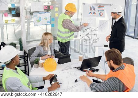 Focused Bearded Male Chief In Suit Listening To Professional Middle Aged Bearded Man Builder Contrac
