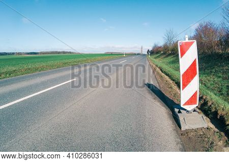 Red White Traffic Warning Mark At The Street. Marks A Seceding Gravel Bed Which Can Be Dangerours Fo