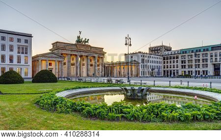 The Famous Brandenburg Gate In Berlin After Sunset With A Fountain