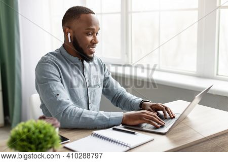 Black Businessman Working On Laptop Wearing Earbuds Sitting At Workplace In Modern Office. Successfu