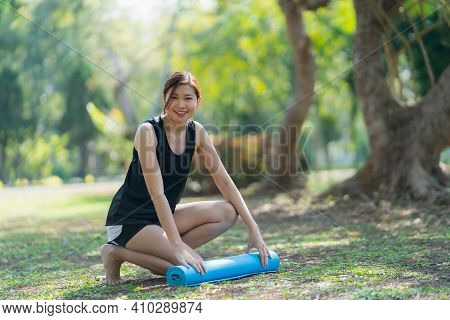 Women Use Rolling Yoga Mat To Do Exercises Yoga In The Park, Sport Yoga Concept
