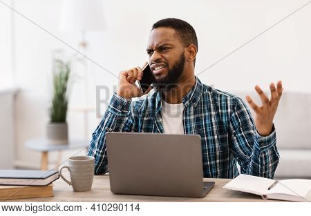 Displeased Black Business Guy Talking On Phone Having Quarrel By Cellphone Sitting At Workplace In M