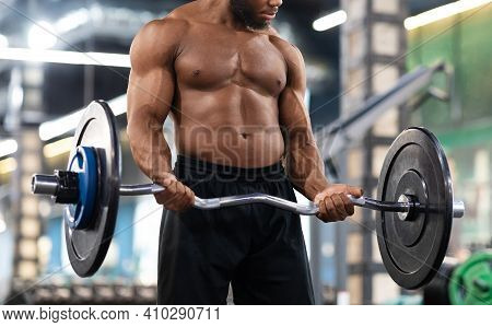 Bodybuilding Concept. Cropped Of Black Muscular Shirtless Guy Lifting Weights In Gym. Unrecognizable