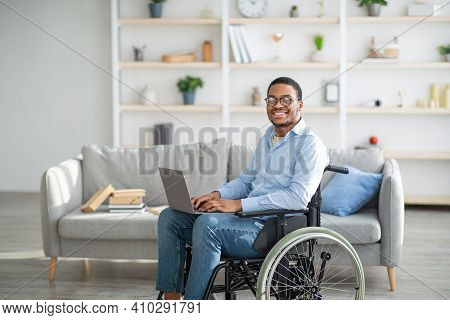 Happy Disabled Black Man In Wheelchair Using Laptop, Working Online From Home, Copy Space. Millennia