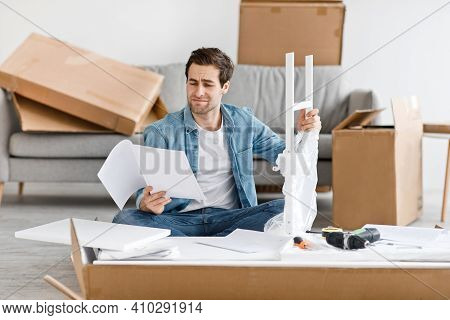 Difficulties And Problems In Assembling Of New Furniture At Home Without Master. Confused Young Male