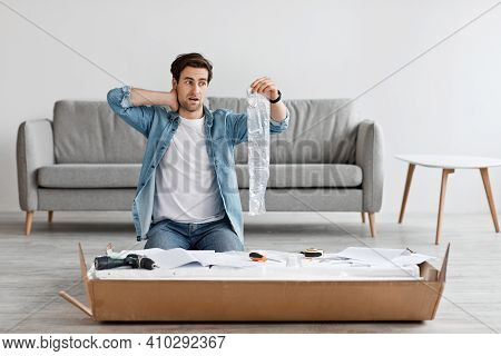 Difficult Assembling Of New Furniture At Home By Yourself. Shocked Confused Handsome Young Man Holdi