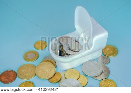 Money In The Toilet. Coins In The Toilet. Blue Background. Throw Away The Money. Flush Money Down Th