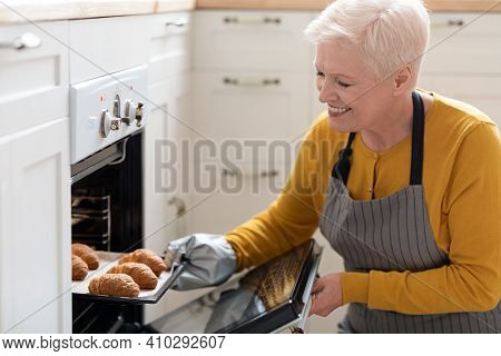 Closeup Of Smiling Elderly Woman Baking Pastry At Home, Taking Delicious Croissants Out Of Oven, Cop