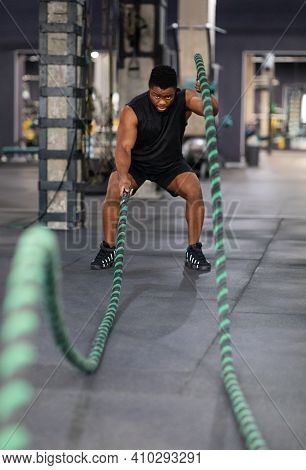 Battle Ropes, Equipment For Gym Concept. Muscular Black Guy Having Work Out With Battle Ropes At Gym