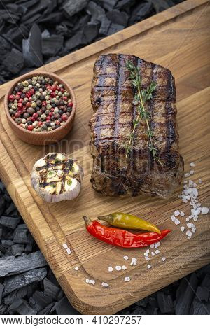 Piece Of Cooked Rump Steak With Spices Served On Wooden Cutting Board