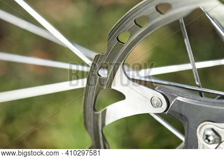 A Macro Shot Of The Front Bicycle Brake Disc, Visible Spokes And A Green Background.