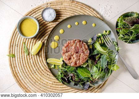 Tuna Tartare With Green Salad, Lime, Avocado And Mustard Sauce Serving On Ceramic Plate On Straw Nap