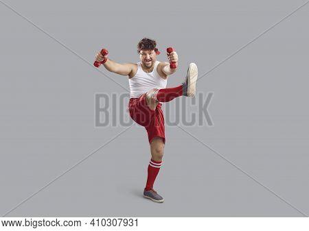 Chubby Man Holding Dumbbells And Doing Cross Leg Swings Standing On Gray Background