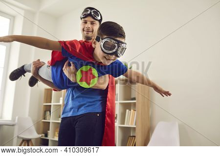Father Helps His Son Fly Like A Superhero. Boy With Pilot Glasses Play Fly With His Dad At Home.