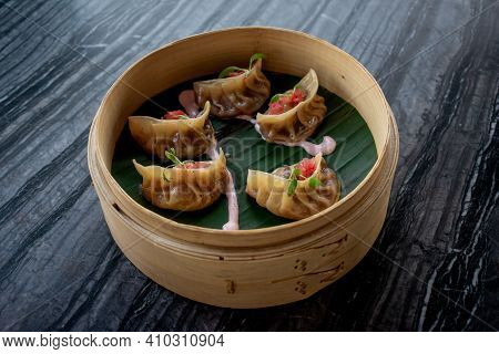 Exquisite Traditional Asian Jiaozi Of Cochinita Pibil And Pickled Onions Inside On A Wooden Bowl On