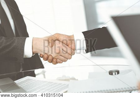 Unknown Diverse Business People Are Shaking Hands Finishing Up Meeting At The Desk In Office, Close-