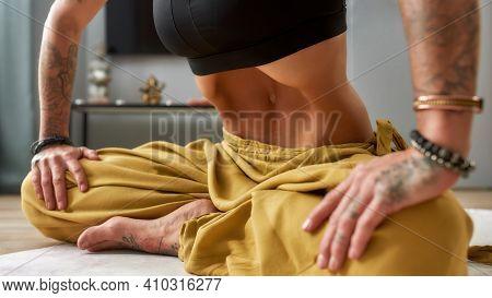 Young Tattooed Girl Practising Uddiyana Bandha Abdominal Lock While Sitting On Floor Mat At Home, Wi