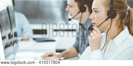 Call Center. Group Of Casual Dressed Operators At Work. Blond Business Woman In Headset At Customer