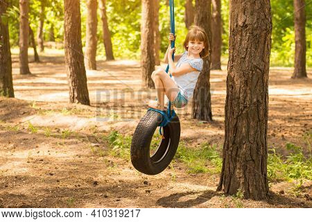 Cute Little Girl Swinging On Wheel Attached To Big Tree In Autumn Forest.