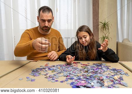 Father And Daughter Dejected By The Difficulty Of Assembling A Puzzle In Their Living Room. Home Con