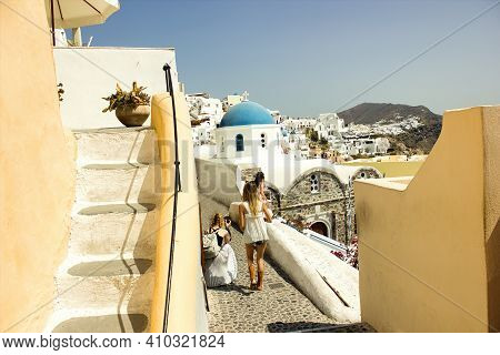 Santorini, Greece - September 11, 2017: Teenager Girls Or Tourists Traveling Together Taking Picture