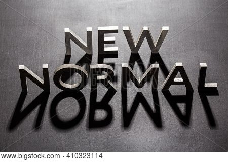 New Normal Word Composed Of Silver Metal Letters On A Flat Matt Black Surface With Shadows Backlit
