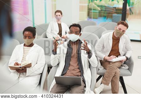 High Angle View At Multi-ethnic Group Of People Wearing Masks And Lab Coats While Listening To Lectu