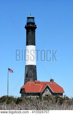 FIRE ISLAND, NY - MAY 23, 2015: Fire Island Lighthouse, Main building, Tower and American Flag.
