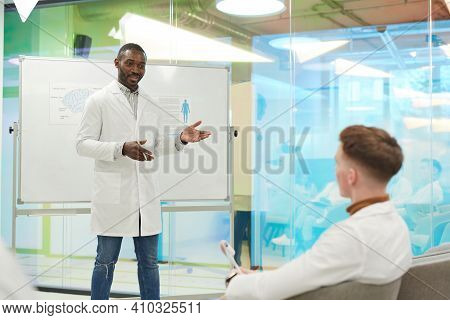 Portrait Of African-american Man Standing By Whiteboard While Giving Presentation During Medical Sem