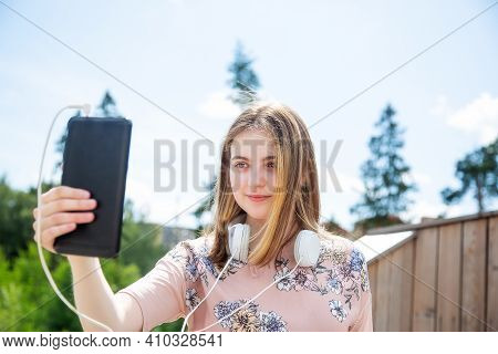 A Young Girl Of 20 Years Old Caucasian Appearance Makes A Selfie On Her Mobile Phone While Sitting O