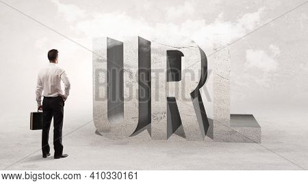 Rear view of a businessman standing in front of URL abbreviation, attention making concept