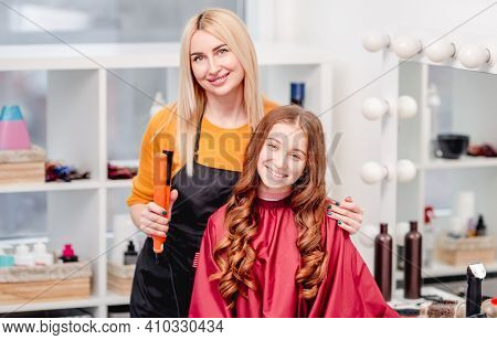 Portrait of hairdresser and model girl with curles after hairstyle together. Professional hairdo in beauty salon