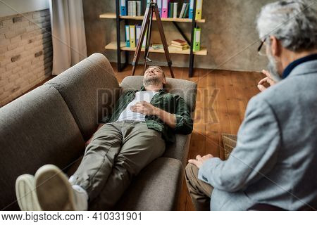 Calm Young Caucasian Man Lying On Couch With Closed Eyes During Psychotherapy Session In Office. Psy