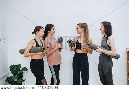 Joyful Friendly Women Socialising At Yoga Club, Holding Rolled Mats Under Arm