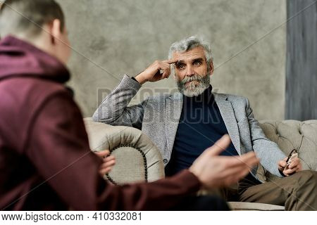 Professional Psychotherapist Listening To Teenage Boy Talking While Sitting On Sofa During Session I