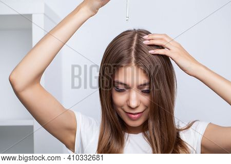 Young Woman Applying Oil Onto Hair At Home