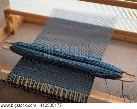 Weaving Shuttle Tool On The Hand Loom. Blue Textile Fabric Weave