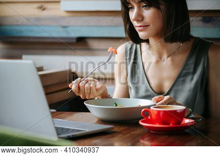 Woman Enjoying Herself, Eating Vegeterian Dish In A Cafe While Watching Laptop.