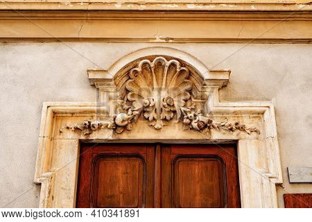 An Architectural Element Above The Entrance, Made In The Style Of A Bas-relief.