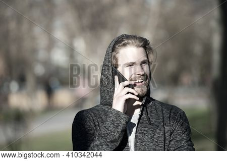 Happy Man Talk On Mobile Phone In Park, Communication. Macho In Hood With Smartphone Smile On Sunny