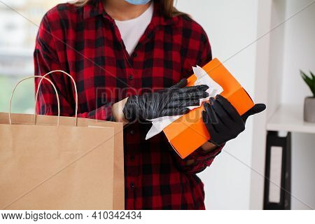 Young Woman Disinfects Parcels Before Unpacking At Home