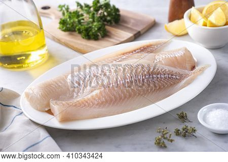 Fresh Icelandic Haddock Fillets On A Plate With Lemon And Parsley.